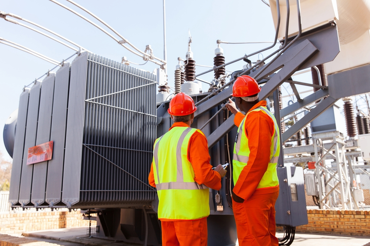 Electricians standing next to a transformer in an electrical power plant.