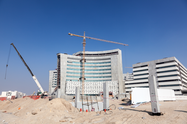 Construction zone with a partially-completed hospital in the background