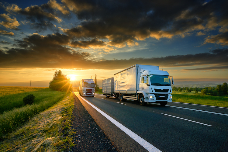 Trucks on highway at sunset