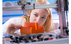 Young female engineer using 3D printer