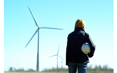 Women engineer with white safety hat standing in a field with wind turbines in the background