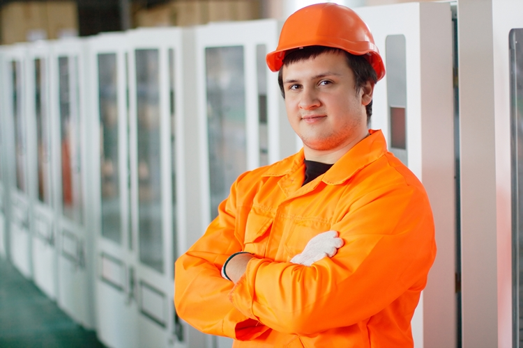 Industrial worker in orange uniform and hard hat standing in front of row of vending machines