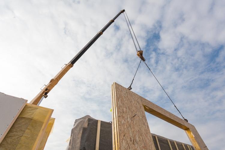 Crane installing structural panel in modular construction job