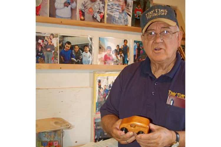 Alton Thacker, founder of Tiny Tim's Foundation for Kids, holding one of his wooden toy cars