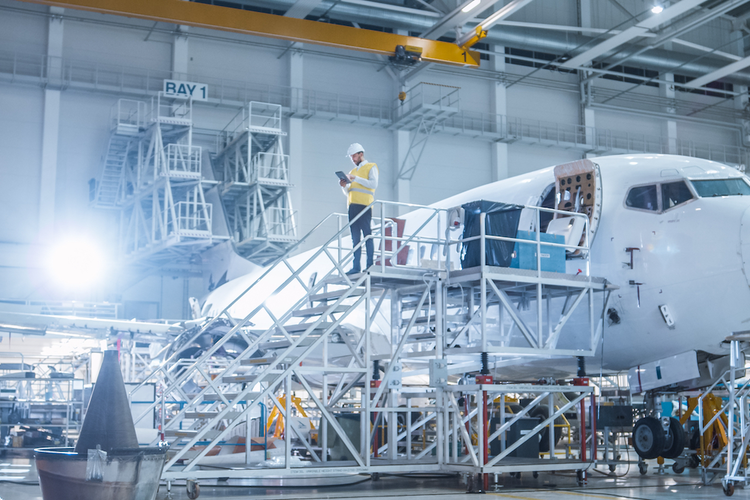 Worker standing next to airplane in hangar