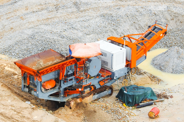 Industrial mechanical conveyor belt/rock crusher in use at construction site