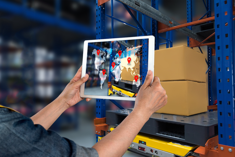 Worker in warehouse using tablet to complete smart tech activities for logistics and supply chain
