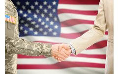 Soldier and civilian shaking hands in front of American flag to represent business Department of Defense and American manufacturers