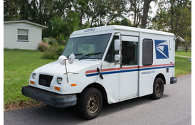 USPS Mail Truck Parked by Mailbox.