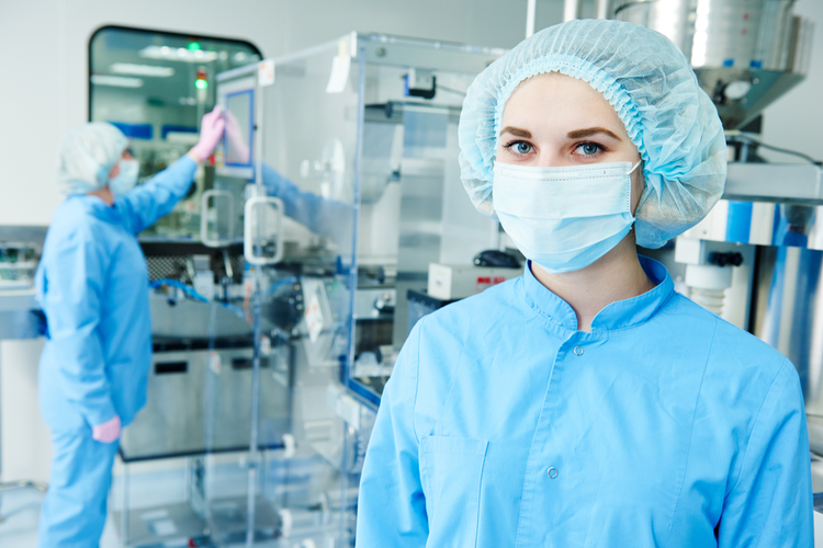 Pharmaceutical workers operating machinery