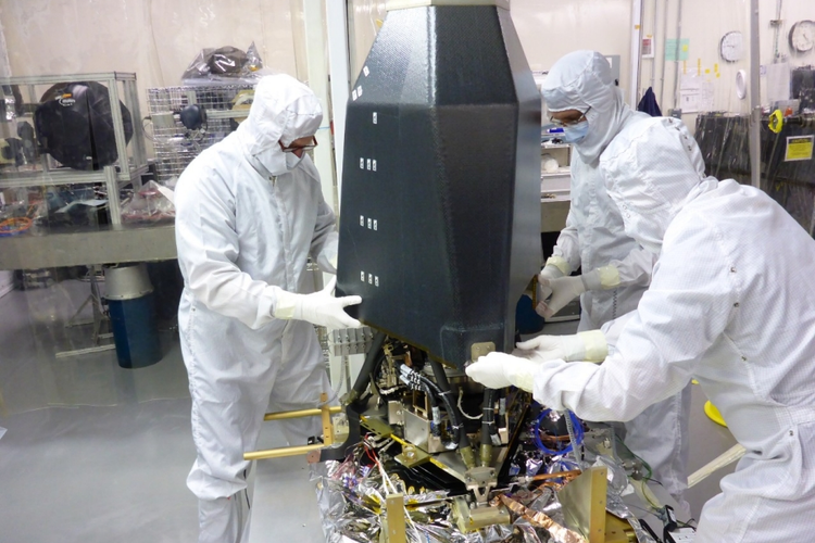 Workers assembling a satellite