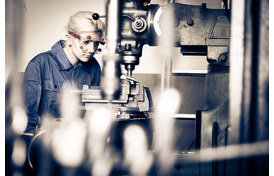 Young female apprentice mechanic working at a milling machine