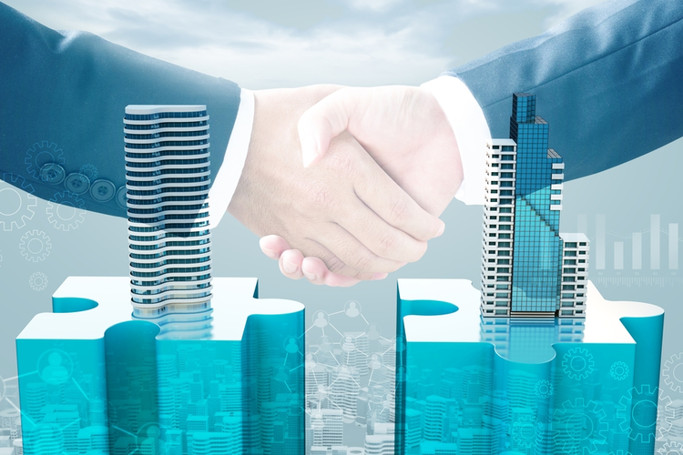 Merger and acquisition business concept: Puzzle pieces with buildings and handshake.