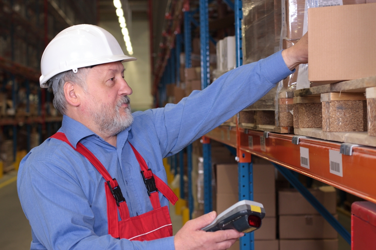 A worker with scanner in a factory checking on inventory.
