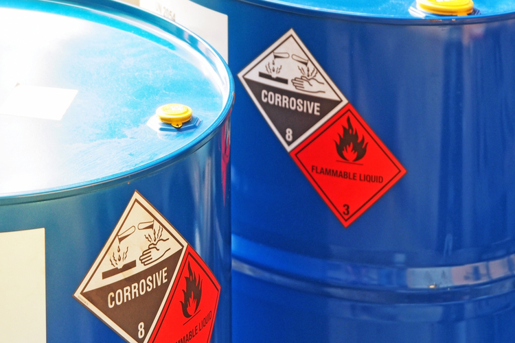 Close-up image of two blue chemical barrels with warning labels.