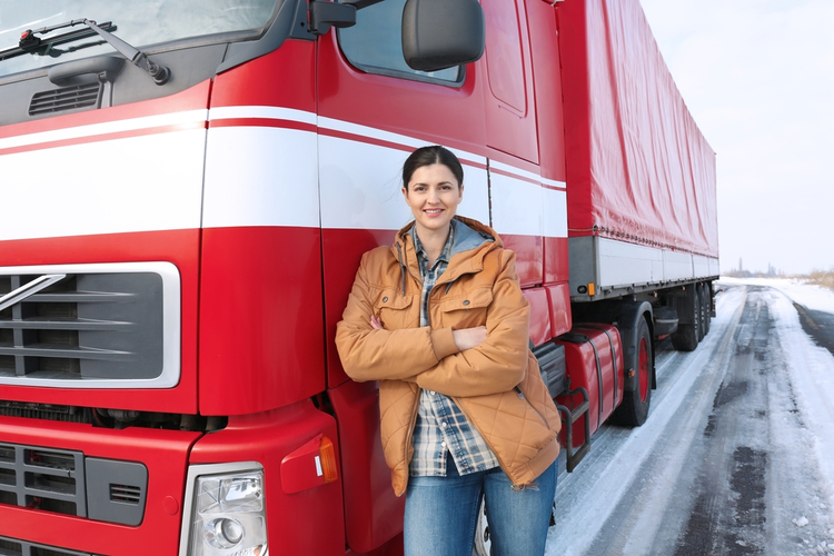 Female driver standing in front of a truck.